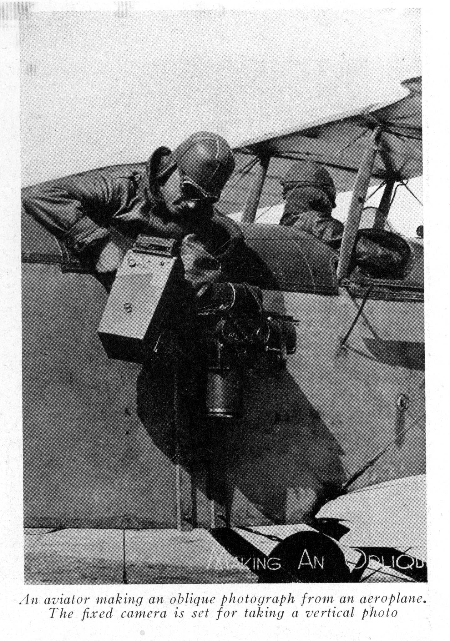 Photograph of an aviator making a photograph from an airplane.