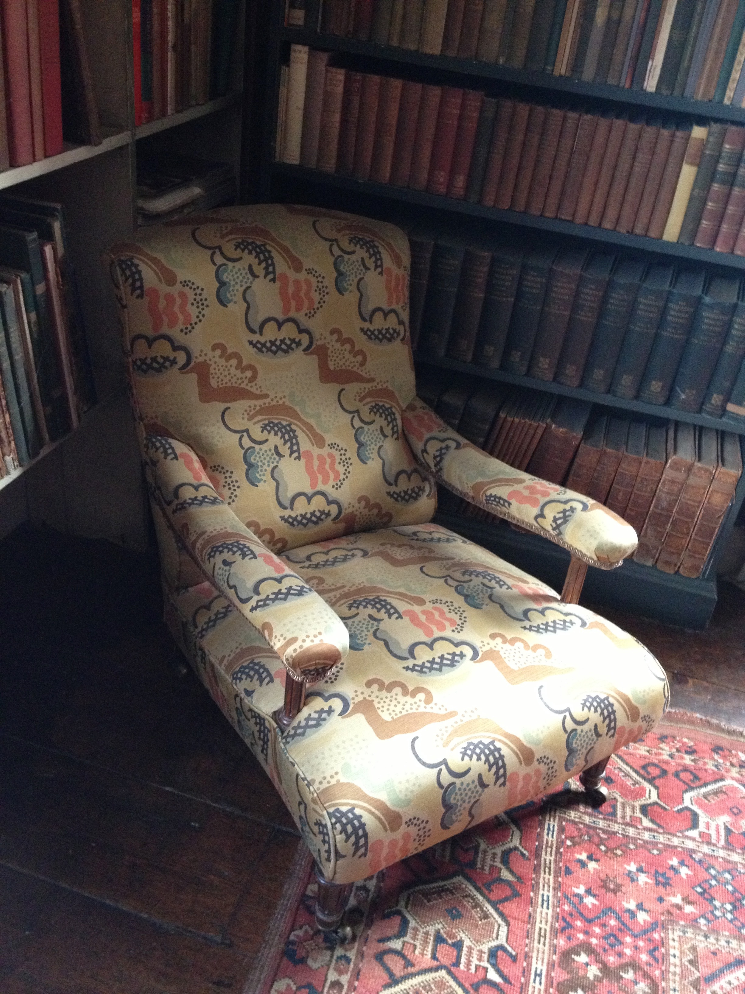 "Low armchair in the library covered in ""Clouds"" fabric by Duncan Grant"