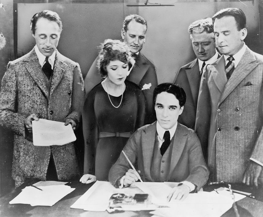 D.W. Griffith, Mary Pickford, Charlie Chaplin (seated), and Douglas Fairbanks at the signing of the contract establishing United Artists motion picture studio in 1919. New York World-Telegram & Sun Newspaper Photograph Collection.