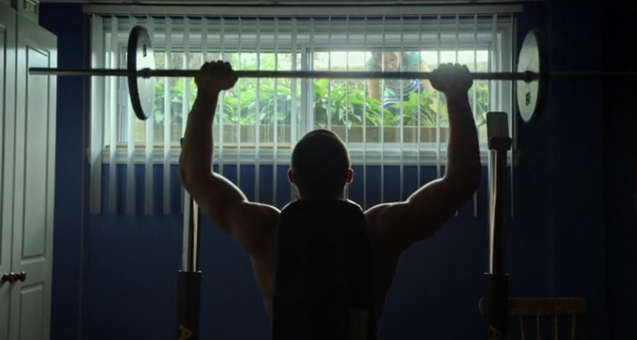Man lifting weights, still from Ta peau si lisse, directed by Denis Côté