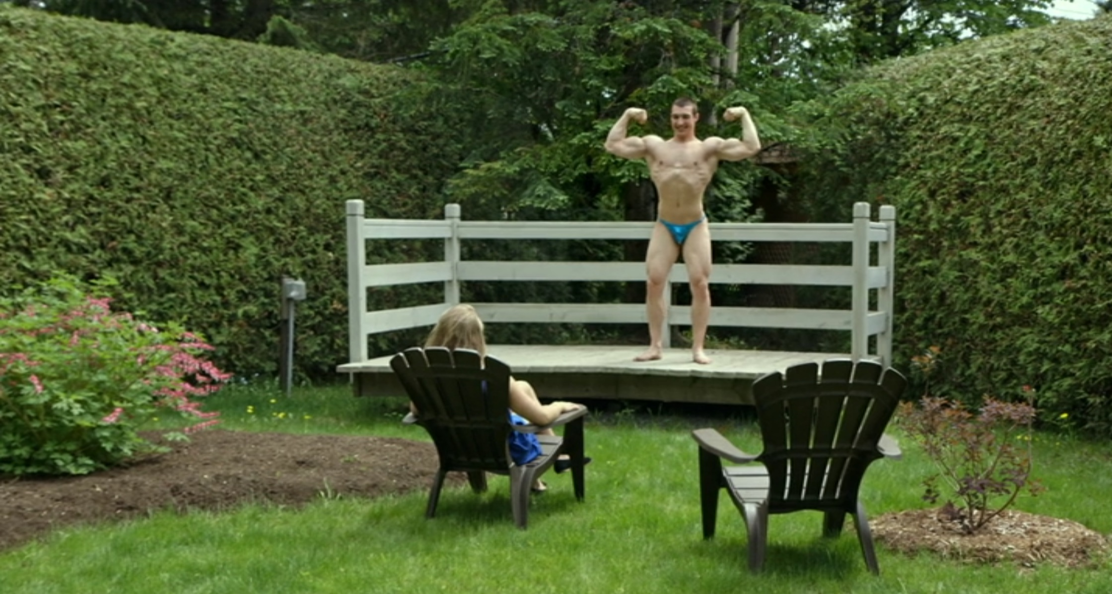 Man flexing on platform, still from Ta peau si lisse, directed by Denis Côté