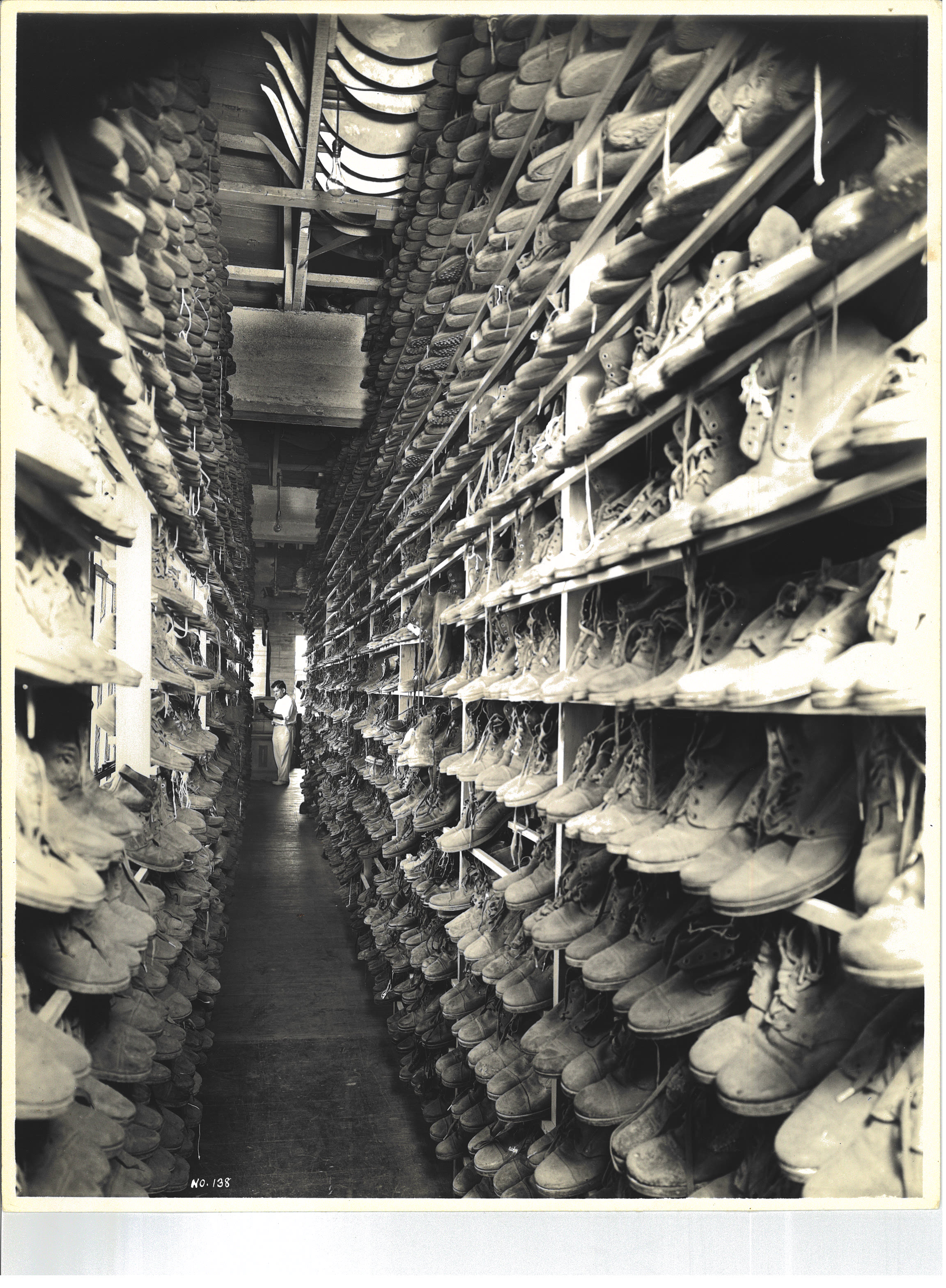 Employee examining boots at Western Costume Company, Bronson Building, Los Angeles, 1935
